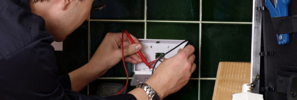 Image of: An electrician checking a plug socket